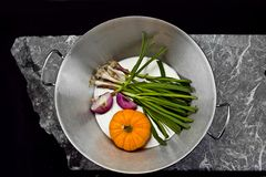 Aerial photo of a saucepan with vegetables on a stone slab.