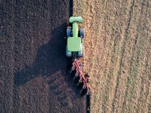Aerial photo of a tractor ploughing a field in a countryside stock images