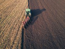 Aerial photo of a tractor ploughing a field in a countryside stock photo