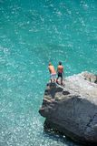Aerial photo of two young boys on rock looking into sea Royalty Free Stock Photo