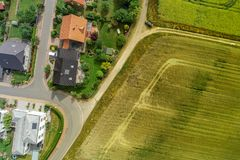 Aerial photograph of two houses on a path behind a field, taken with the drone stock images