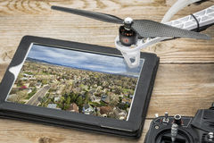 Aerial photography concept - cityscape. Drone aerial photography concept - reviewing aerial picture of residential area on a digital tablet with a drone rotor stock photos