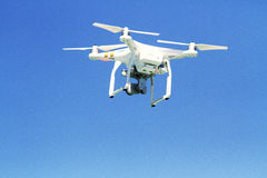 Aerial photography by drone motion in the air in motion. White drone flying with camera record liens against blue sky stock photo