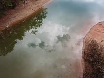 Aerial photography of lake water and shore. Aerial photography of lake with clouds and trees reflecting off of water Stock Images
