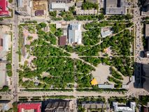 Aerial photography of a modern city park. With green trees, attractions, high-rise buildings, roads with cars on a warm summer day. Helicopter drone shot royalty free stock image