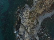 Aerial photography of the Sardinia coast during a summer sunset. Small waves on the rocks taken with a drone royalty free stock image