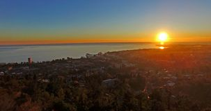Aerial photography of the urban landscape with. A beautiful sunset over the sea stock footage
