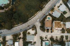 Aerial Photography of Vehicles on Road Beside Houses stock images