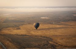 Aerial picture of aerostatic balloon above the field royalty free stock image