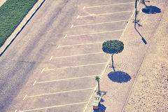 Aerial picture of an empty parking lot. Vintage toned aerial picture of an empty parking lot with trees and pavement Royalty Free Stock Photos