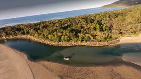 Aerial picture image of people fishing noosa river. People fishing in dinghy boat along Noosa River alongside bike and walking trail at low tide Royalty Free Stock Photos