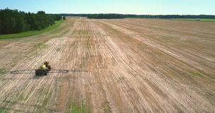 Fertilizer spreader with long bars drives along harvested field. Aerial picture tractor fertilizer spreader with yellow tank and long bars drives along vast stock footage
