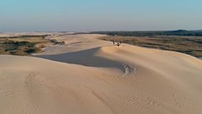 Aerial picture of young people standing on the peak of a sand dune in beautiful desert environment. Santa Cruz, Bolivia - SEPT 5 2018: aerial picture of young stock photo