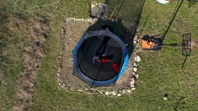 Aerial view of mother with her daughter having fun and jumping on trampoline by drone stock footage