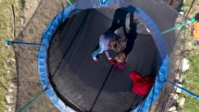 Aerial view of mother with her daughter having fun and jumping on trampoline by drone stock video