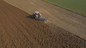 Aerial - Preparing field for planting crops with agricultural machinery stock video