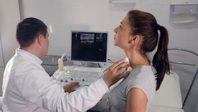 Aerial of the process of  ultrasound examination of the larynx. Aerial of the doctor making the  ultrasound examination of the  larynx of a woman stock video