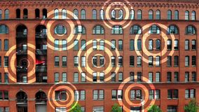 Aerial profile view of apartment building with wifi waves. A side profile aerial view of a city red brick apartment building with WiFi waves emanating from stock video footage