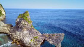 Aerial pull away shot with drone of marine beach landscape with rocky cliff and wild blue sea in stunning beautiful nature. And paradise holidays travel stock footage