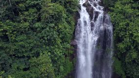 Aerial crane style tilt down shot with drone above beautiful Bali paradise waterfall and jungle rainforest in Asia travel. Aerial pull away and tilt down shot stock footage
