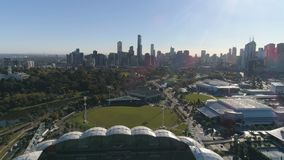 Aerial pullback shot of Melbourne city downtown panorama and Melbourne Rectangular Stadium, Melbourne, Victoria, Australia
