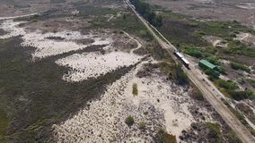 Aerial. Rails for a train from the sky, through the Ria Formosa to the beach Barry. stock video