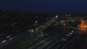Aerial railway wagons at the railroad yard. View from the sky on railroad at night. The railway station aerial. 4K stock video footage