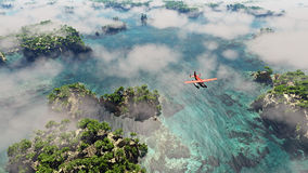 Aerial of red airplane flying over coastal landscape with rocks and trees. Stock Photography