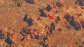 Aerial of red airplane flying over dry desert landscape. Stock Images