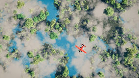 Aerial of red airplane flying over forest with lakes. Royalty Free Stock Photos