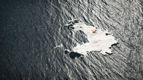 Aerial of red airplane flying over melting iceberg. Stock Photos