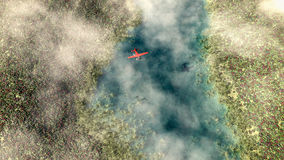 Aerial of red airplane flying over spring meadow with river. Royalty Free Stock Image