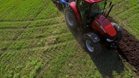 Aerial of red tractor plowing soil on green agricultural field