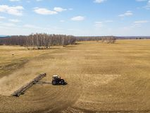 Aerial of Red tractor with a trailed plow for mowing and weeding fields for the agro-industry of yellow color under the blue sky,. A clear spring day stock image