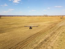 Aerial of Red tractor with a trailed plow for mowing and weeding fields for the agro-industry of yellow color under the blue sky,. A clear spring day stock photos