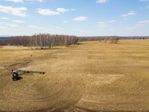 Aerial of Red tractor with a trailed plow for mowing and weeding fields for the agro-industry of yellow color under the blue sky,. A clear spring day royalty free stock image