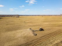 Aerial of Red tractor with a trailed plow for mowing and weeding fields for the agro-industry of yellow color under the blue sky,. A clear spring day royalty free stock photos
