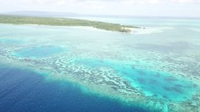 Aerial of Remote Island and Surrounding Reef in Wakatobi. A remote island is surrounded by reefs in Wakatobi National Park in Indonesia. This region harbors stock footage