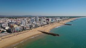 Aerial. Resting tourists on the beach Quarteira, filmed from the sky. stock footage