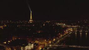 AERIAL: Reverse Drone Flight from Eiffel Tower,Tour Eiffel in Paris, France at Night with City Lights. 4K stock video