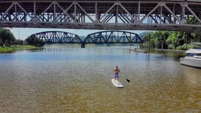Aerial Reverse View of Man on Stand Up Paddle board on River. An aerial reverse view of a man on a stand up paddle board on a Pennsylvania river in the summer stock footage