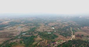 Aerial of Rice field, North of Thailand. Aerial view of agriculture in north of Thailand, after harvest season with villagers house and little fog stock video footage