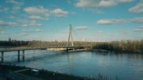 Aerial rising shot of Vistula river embankment and Holy Cross cable bridge in Warsaw, Poland Royalty Free Stock Photos