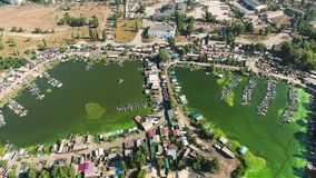 Aerial of river bay polluted with green algae with huts and boat docks on banks. Aerial of river bay polluted with green algae with fisherman huts and boat docks stock footage
