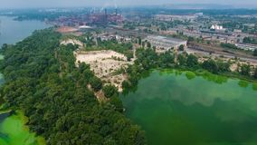 Aerial of river polluted with green algae near big industry zone. Ecology, waste water, environmental problems stock video