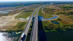 Aerial road traffic. Aerial view road above river landscape. Highway landscape. Aerial road bridge above river. Top view cars and truck moving on highway bridge stock footage