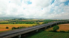 Aerial view of driving vehicles along the highway between yellow and green grass. Aerial view of fields and rural settlements by summer sunny day in Tuscany stock video footage