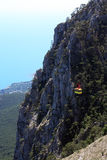 Aerial Ropeway. Yellow overhead cable car on background with very high mountain and sea Stock Photography