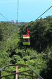 Aerial Ropeway. Yellow overhead cable car moving from mountain to sea above forest Royalty Free Stock Images
