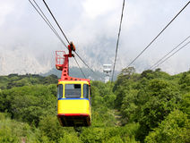 Aerial ropeway cabin. Empty yellow aerial ropeway cabin going down mountain Royalty Free Stock Image